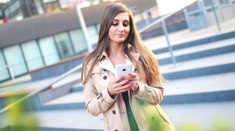 kobita ze smartfonem w plaszczu