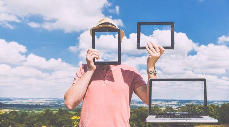 mężczyzna z dwoma tabletami i laptop