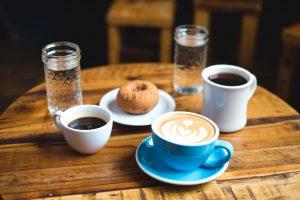 Kawa, woda i słodka przekąska na biurku
