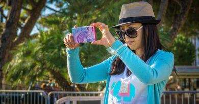 dziewczyna w niebieskim swetrze i kapeluszu robiąca zdjęcie na Instagram
