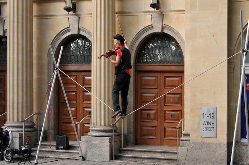 linoskoczek grający na skrzypcach w trakcie przejścia po linie