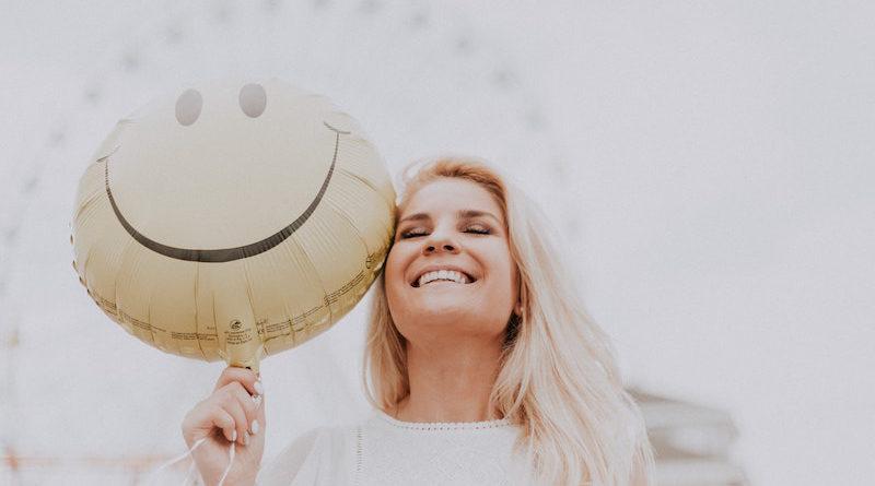 uśmiechnięta blondynka z uśmiechniętym balonem