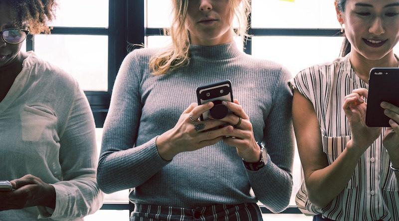 Trzy dziewczyny korzystające z telefonów komórkowych