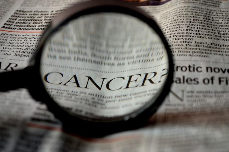 Gazeta z lupą powiększającą słowo Cancer/ Rak